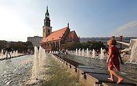 A girl playing in the fountains of the Alexanderplatz at sunset, with the Marienkirche or St Mary's Church, originally 13th century but comprehensively restored in the 19th and 20th centuries, behind, Berlin, Germany. Picture by Manuel Cohen