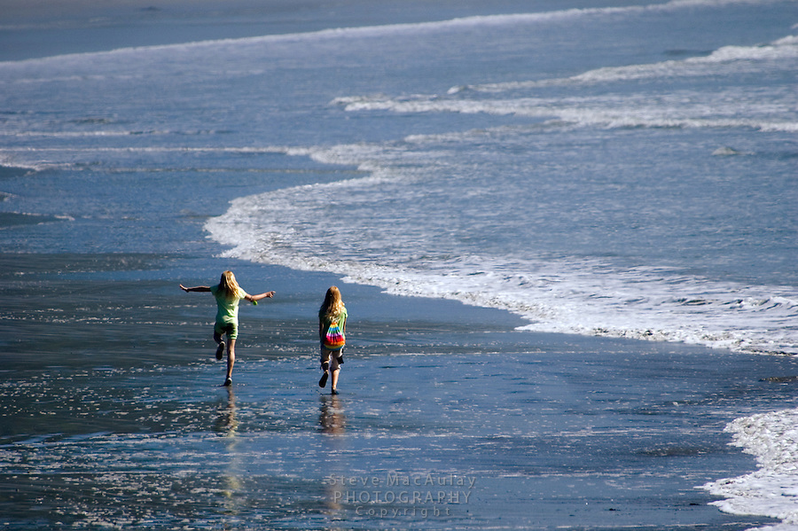 Two young girls skipping down the beach and playing in the waves. Olympic National Park, WA.