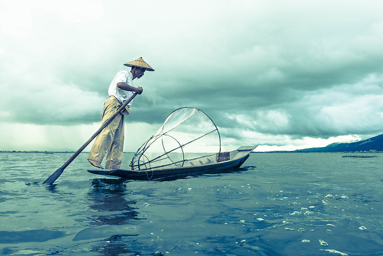 A fisherman rows a boat on the Inle Lake at Nyaungshwe township in Shan State, Myanmar, November, 2013. Leg rowing of the Intha people at Inle Lake is one of the major tourist attractions of Myanmar.