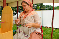 Daughter of 2nd Regiment of the Albany County Militia soldier, handweaves cotton tape on a Box Loom, used for garters, bonnet straps, drawstrings, shoestrings and more, at a Revolutionary War encampment, Fort Ticonderoga, New York, USA.