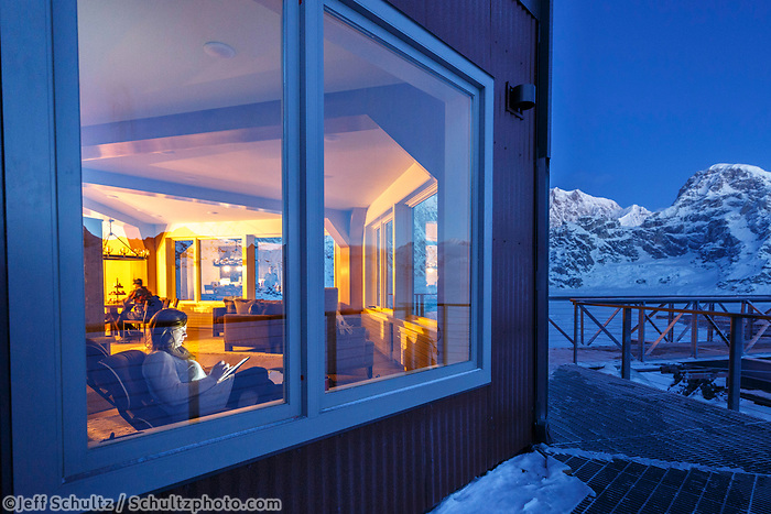 woman sits indside of the Sheldon Chalet on computer and watches the dawn break in the Ruth Glacier and Amphitheater in the Alaska Range.  Winter <br /> <br /> Photo by Jeff Schultz/SchultzPhoto.com  (C) 2017  ALL RIGHTS RESERVED