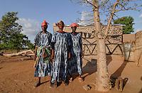 BURKINA FASO Dorf Sesuala bei Pó , Ethnie Kassena , Frauen Kooperative verarbeiten Karite bzw Shea Nuesse zu Shea Butter, Frau Avi Nabila mitte Leiterin der Kooperative und Frau Abakola Adakta links, vor kleinem Baobab Baum und Lehmhaus mit Kassena Style Bemalung - BURKINA FASO , village Sesuala near Pó , ethnic Kassena , women cooperative produce shea butter from shea nuts of Karite tree, right Mrs. Avi Nabila , leader of cooperative