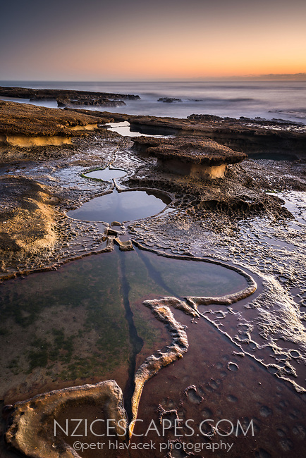 Limestone rocks with water pools on Truman Track under sunset in Punakaiki, Paparoa National Park, West Coast, New Zealand