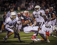 ST. Rita quarterback Tommy Mister is brough down for a loss by Deontae Brown, left, and Colin Knusta, right, during the first quarter Friday night
