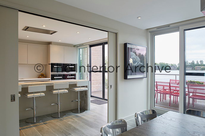 A set of sliding doors leads from the dining room area to a stylish, uncluttered kitchen decorated in neutral tones.