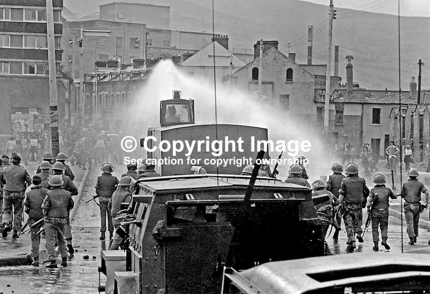 British soldiers use a water canon against rioters on the Lower Falls Road area of Belfast. The rioting broke out following a People's Democracy march which was prevented by soldiers and police from entering the city centre in Belfast, N Ireland. The march was in support of PD leaders Michael Farrell and Tony Canavan who were on hunger strike seeking political status in Belfast's Crumlin Road Jail.  29 July 1973, 197307290522h<br /> <br /> Copyright Image from Victor Patterson, 54 Dorchester Park, <br /> Belfast, UK, BT9 6RJ<br /> <br /> t1: +44 28 9066 1296 (from Rep of Ireland 048 9066 1296)<br /> t2: +44 28 9002 2446 (from Rep of Ireland 048 9002 2446)<br /> m: +44 7802 353836<br /> <br /> e1: victorpatterson@me.com<br /> e2: victorpatterson@gmail.com<br /> www.victorpatterson.com<br /> <br /> Please see my Terms and Conditions of Use at www.victorpatterson.com. It is IMPORTANT that you familiarise yourself with them.<br /> <br /> Images used on the Internet must be visibly watermarked i.e. &copy; Victor Patterson<br /> within the body of the image and copyright metadata must not be deleted. Images <br /> used on the Internet have a size restriction of 4kbs and will be chargeable at current<br />  NUJ rates unless agreed otherwise.<br /> <br /> This image is only available for the use of the download recipient i.e. television station, newspaper, magazine, book publisher, etc, and must not be passed on to any third <br /> party. It is also downloaded on condition that each and every usage is notified within 7 days to victorpatterson@me.com<br /> <br /> The right of Victor Patterson to be identified as the author is asserted in accordance with The Copyright Designs And Patents Act (1988).