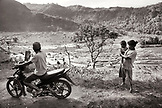 INDONESIA, Flores, people gather on the roadside with views of a valley filled with rice fields and workers in the distance, Waturaka Village