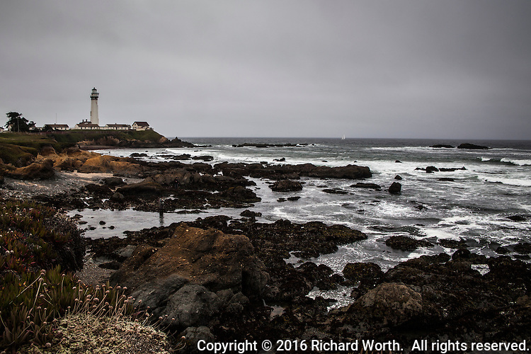 Pigeon Point Lighthouse under heavy overcast and with mist in the air.  On the horizon, barely visible, is a sailboat.
