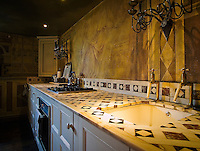 The walls of the kitchen have been painted with a classical trompe l'oeil scene