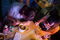 """A group of students from Hubei Province eat fried noodles from a franchise food vendor at Deyi World plaza near the Jiafengbei central business district in Yuzhong district, Chongqing, China. The group, ages 18-20, had spent their summer vacation as volunteer teachers in Guizhou Province and stopped in Chongqing on the way back to their hometowns. Ge Xin Wei (in blue) said that they came to Deyi World because they'd heard the area was a popular place to go at night. """"The food is delicious and spicy,"""" she said."""