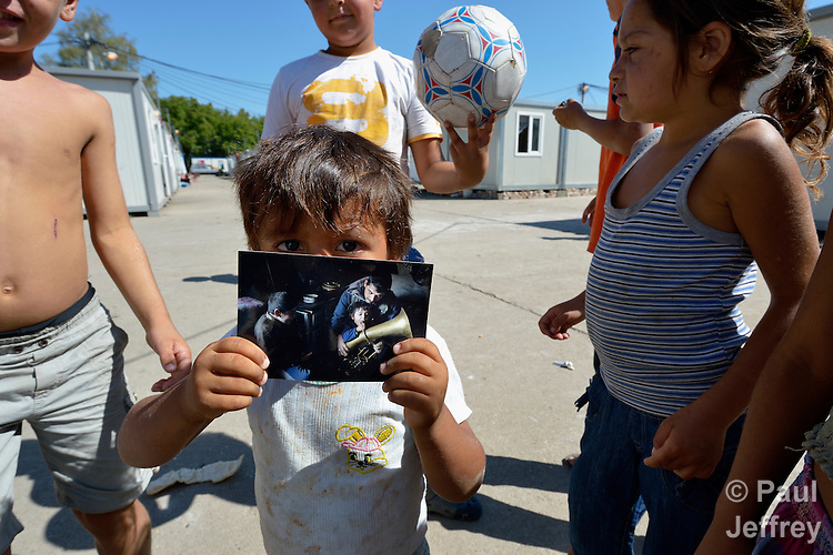 Three-year old Boban Pesic holds a photo of himself in his old home in an urban squatter settlement in Belgrade, Serbia. He and his family were evicted from there in 2012, and now they live in a shipping container in Makis, a village outside the capital. Their eviction made way for construction of new apartments and office buildings.