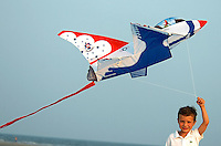 A young boy flies an airplane-shaped kite on the windy ocean beach on Sullivan's Island, SC.