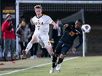 COLLEGE PARK, MD - NOVEMBER 21: Josh Plimpton #7 of Iona boots the ball past Fola Adetola #29 of Maryland during a game between Iona College and University of Maryland at Ludwig Field on November 21, 2019 in College Park, Maryland.