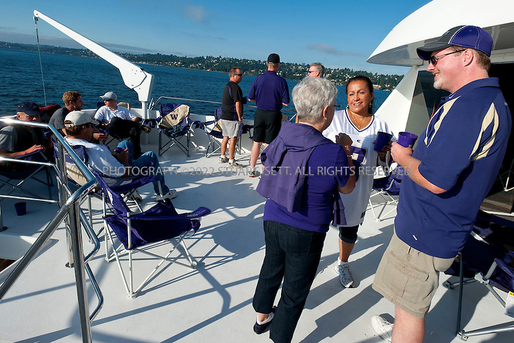 9/24/2011--Seattle, WA, USA...The Big Dawg heads across Lake Washington from Mercer Island to Husky Statium...The 'Big Dawg', owned by Lisa and Tim Kittilsby, is the biggest, most prominent boat that attends regular boat tailgate parties on docks near the UW (University of Washington) Husky Stadium. Up to 500 boats will tie up outside Husky Stadium on football game days, ranging from from small boats to huge yachts. The Big Dawg is a 92-foot, two-story yacht that dominates the tailgate parties...The tradition started when Lisa and Tim Kittilsby's parents, Frank and Jeanie Miles, took a 23-foot boat called The Mixer to a game over 40 years ago...©2011 Stuart Isett. All rights reserved.