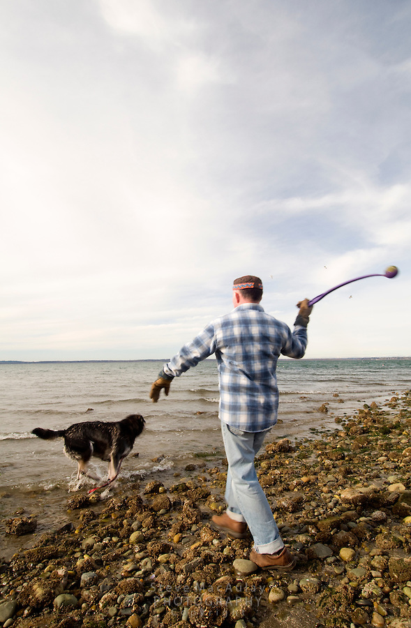 Man throwing ball for his dog, Marine Park, Bellingham, WA
