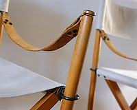 A close up of a pair of white canvas director's chairs