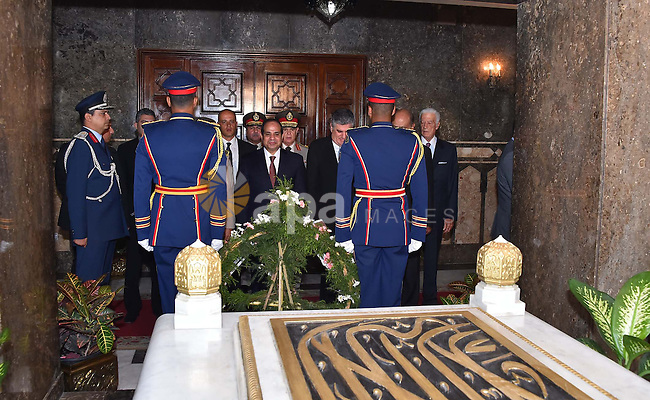 A handout picture released by the Egyptian Presidency shows Egyptian President Abdul Fattah al-Sisi (C) paying his respects in front of the grave of former Egyptian President Gamal Abdel Nasser during a ceremony at the memorial of the Unknown Soldier and tombs of late Egyptian presidents on October 4, 2015 in Cairo, as part of the celebrations marking the 42th anniversary of October War Victory. Photo by Egyptian President Office
