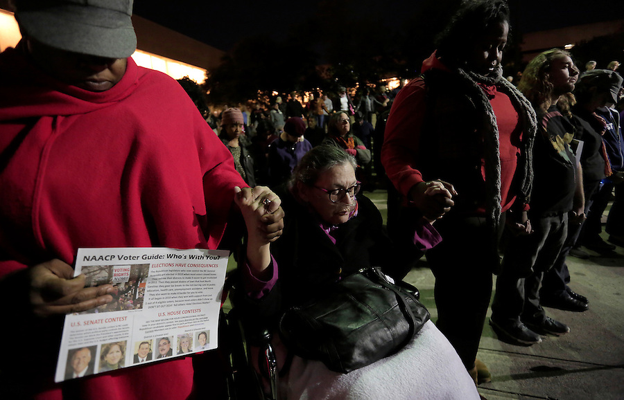 GREENSBORO, NC - NOVEMBER 3:   Dr. Kathleen Casey, center, holds hands and prays with Lissa Harris (cq Lissa), left, and others during a Moral March to the Polls rally sponsored by the North Carolina NAACP in Greensboro, NC, on Monday, November 3, 2014, while Harris also holds a voter's guide on the eve of Election Day.  (Photo by Ted Richardson/For The Washington Post)