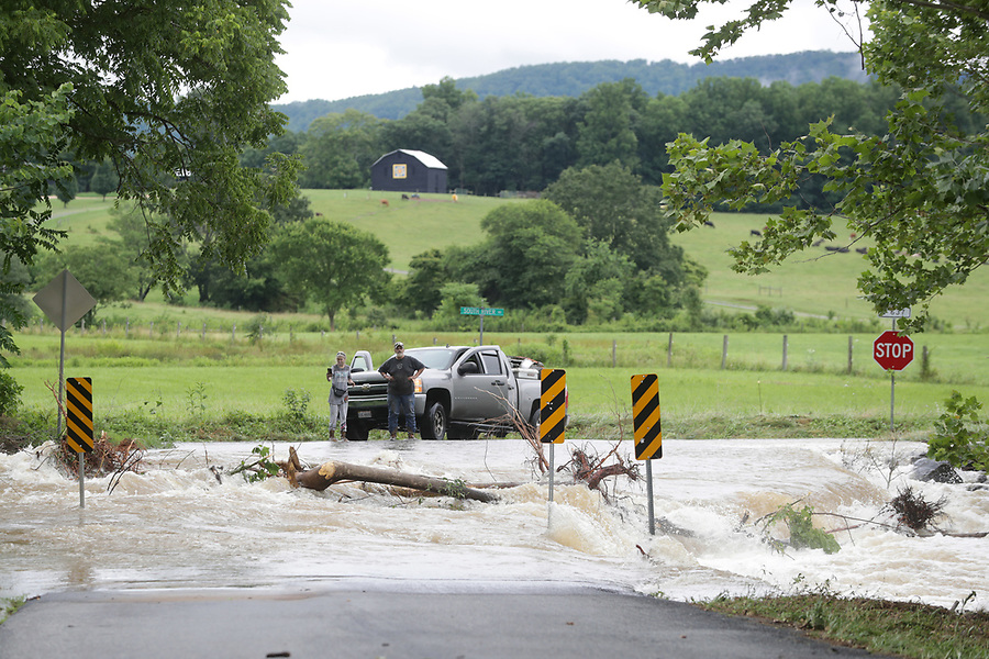 People stop and take pictures of heavy flood waters from the South River at the intersection of Octonia Road and South River Road Friday in Greene County. Photo/Andrew Shurtleff Photography, LLC