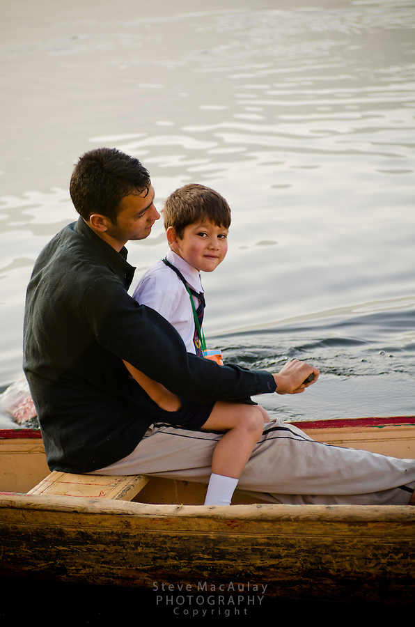 Older brother taking younger brother to school on traditional shikara, Dal Lake, Srinagar, Kashmir, India.