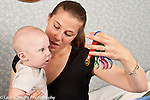 5 month old baby boy with mother interested in toy she holds up for him