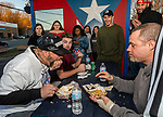 WATERBURY, CT. 12 January 2020-011220BS18 - A group of people watch, from left, Baked potato contestant Jose Rivera, shoves the last remaining spuds of his baked potato into his mouth as Evan Scarzella and Steve Shircliff look on, during the baked potato eating contest at the Little Puerto Rico Restaurant in Waterbury on Sunday. The person who ate the whole potato, skin and all, the fastest, won $50 and a championship belt. Bill Shettle Republican-American