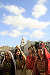 Christmas in Bethlehem, Palestinian girls in traditional dresses in Manger Square, the Church of the Nativity is in the background