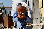 A Palestinian man drinks water from a water tank in the West Bank village of Um Alkhair south of Hebron on August 17, 2016. Photo by Wisam Hashlamoun