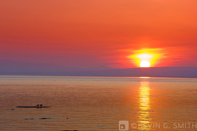 Photo of the sun setting over Mount Susitna reflected in the waters of Knik Arm as seen from Earthquake park, late winter, Southcentral Alaska, USA.
