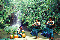 Hula dancers with kupuna elder and ipu gourds on lauhala mats at pool in front of waterfall