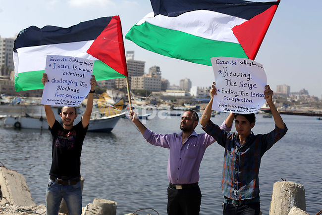 Palestinian fishermen hold banners flags during a rally inside the port of Gaza to protest on the Israeli siege on the Gaza Strip and the five-year anniversary of the entry of first two ships solidarity with Gaza, in Gaza city, on Aug. 22, 2013. Photo by Ashraf Amra