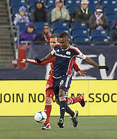 New England Revolution midfielder Juan Agudelo (10) dribbles as Toronto FC forward Jeremy Brockie (22) defends. In a Major League Soccer (MLS) match, the New England Revolution (blue) defeated Toronto FC (red), 2-0, at Gillette Stadium on May 25, 2013.