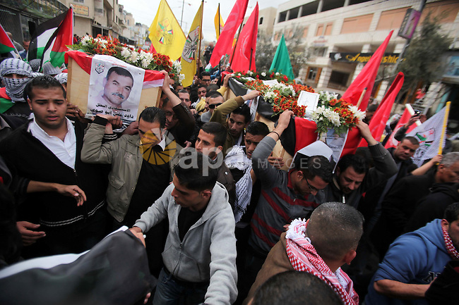Palestinians carry coffins containing the remains of Ayat al-Akhras and Daoud Abu Swai during their funeral in Deheishe refugee camp in the West Bank town of Bethlehem February 3, 2014. Last month, Israel began to exhume the remains of a number of Palestinian militants, including al-Akhras and Swai, to return them to their families for burial in a move that could help ease some tension between the adversaries. Al-Akhras and Swai, blew themselves up in two separate attacks against Israelis some 12 years ago in Jerusalem. Photo by Mamoun Wazwaz