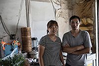 Restaurant owner and former truck driver Dong Haiqiang and his wife at their small restaurant in Xingxing village on the outskirts of Shanghai,  China on 14 August 2015.  As China's sputtering economy has beginning to affect employment, many migrants who used to live in the village to work on Shanghai's numerous construction sites and factories are beginning to thin out.