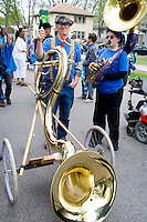 Band members holding mobile Sousaphone tuba on wheels. MayDay Parade and Festival. Minneapolis Minnesota USA