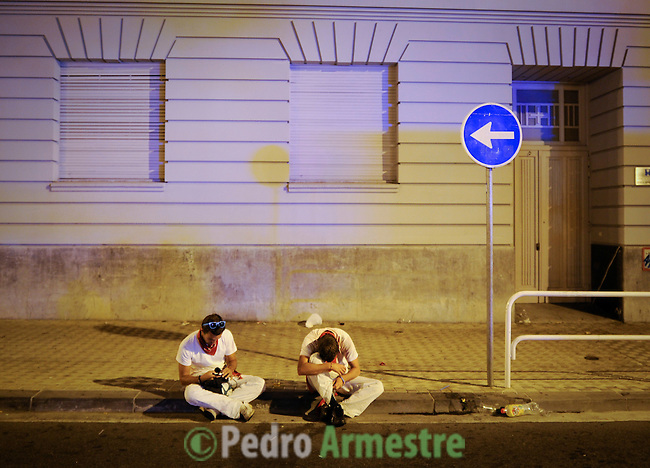 Men sleep before the first bull run of the San Fermin Festival, on July 7, 2012, in Pamplona, northern Spain. The festival is a symbol of Spanish culture that attracts thousands of tourists to watch the bull runs despite heavy condemnation from animal rights groups. (c) Pedro ARMESTRE