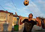 A man prepares to head a soccer ball while playing football in the street in the largely Roma neighborhood of Gorno Ezerovo, part of the Bulgarian city of Burgas. Residents here don't self-identify much as Roma, because of the negative connotations associated with the word, so many refer to themselves as a Turkish-speaking minority.