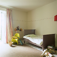 A childs bedroom in neutral tones. The room is furnished with a simple painted single bed and green chair.