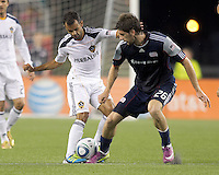Los Angeles Galaxy midfielder Juninho (19) dribbles as New England Revolution midfielder Stephen McCarthy (26) challenges. In a Major League Soccer (MLS) match, the Los Angeles Galaxy defeated the New England Revolution, 1-0, at Gillette Stadium on May 28, 2011.