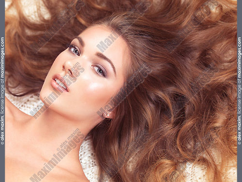 Beauty concept of a young beautiful woman lying down with long brown hair around her