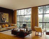 In the living room a painting by Stefan Knapp hangs above a beige leatherette sofa designed by Gwynne