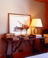 Detail of a console table in the bedroom with antique books and ceramic dishes
