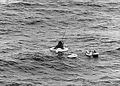 United States Air Force pararescue personnel of the 41st Air Rescue Squadron are pictured as they completed the operation of fastening the flotation collar to support the Aurora 7 spacecraft at sea following the May 24, 1962 MA7 orbital flight of Lieutenant Commander M. Scott Carpenter.<br /> Credit: NASA via CNP