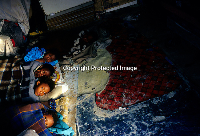 Unidentified children wake up in their one-roomed shack on July 11, 2001 in Site B in Khayelitsha, a township about 35 kilometers outside Cape Town, South Africa. About one million people live in this township, mostly in bad conditions. Khayelitsha is one of the poorest and fastest growing townships in South Africa. People usually come from the rural areas in Eastern Cape province to find work as maids and laborers. Most people don't find work and the unemployment rate is very high..
