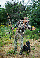 Sean Simmons directs his dog Maverick to fetch a dove during opening day of dove hunting season on Kansas State Wildlife fields near Wamego, Kansas, Sunday, September 1, 2013. Opening day is known for being a festive day of hunting with family and friends. <br /> <br /> Photo by Matt Nager