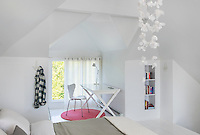 A modern, white bedroom with a pitched ceiling and painted floorboards, which give the room a Scandinavian feel. A classic white Arne Jacobsen butterfly back chair and a simple table are placed in front of a window. A round pink rug provides a spot of bold colour.