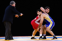 11 DEC 2011 - LONDON, GBR - Soslan Ktsoev (RUS) (in blue) prepares to take the advantageous position at the start of an overtime period in the men's 84kg category final against Sharif Sharifov (AZE) (in red) at the London International Wrestling Invitational and 2012 Olympic Games test event at the ExCel Exhibition Centre in London, Great Britain (PHOTO (C) NIGEL FARROW)