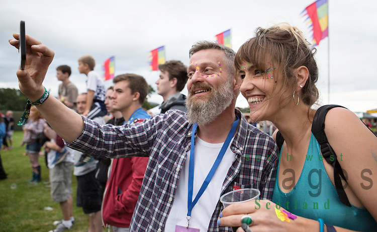 Electric Fields music festival at Drumlanrig Castle near Dumfries Scotland. Couple taking a selfie