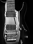 Artistic closeup of an electric guitar Ibanez with chrome parts on black background black and white photo