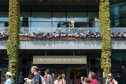 05.07.2013. Wimbledon, London England.  The Wimbledon Tennis Championships 2013 held at The All England Lawn Tennis and Croquet Club, London, England, UK.  Fans enjoying champagne above the Wimbledon shop prior to the start of the tennis.